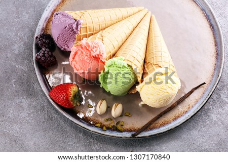 Set of ice cream scoops of different colors and flavours with berries, nuts and fruits and vanilla