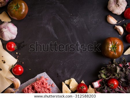 Set of ingredients for italian lasagna. Black food background with free space for text. Pasta, tomatoes, fresh ground meat, parmesan, mozzarella, basil, garlic on a rustic chalkboard. Overhead