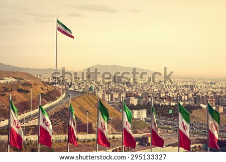 Set of Iran flags in Front of Tehran Skyline and one large flag in the background at sunset with orange warm tone. Stock fotó ©