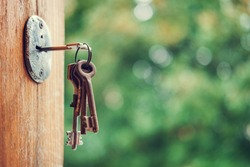 Set of keys in the keyhole, blurry green nature background,