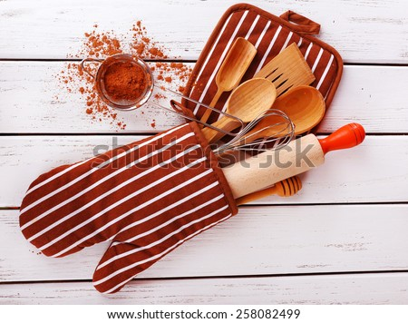 Set of kitchen utensils with cocoa in mitten on wooden background stock photo