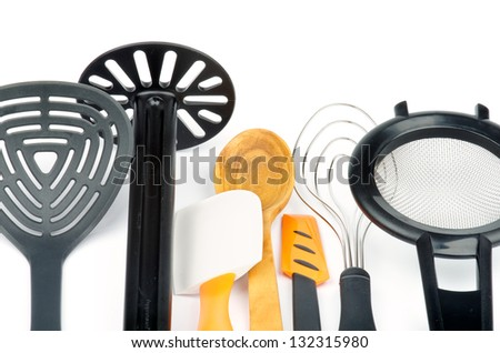 Set of Kitchen Utensils with Slotted Spoon, Potato Musher, Spatula, Wooden Spoon, Cream Spatula, Wire Whisk and Colander isolated on white background