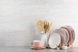 Set of kitchenware on table near light wall, space for text. Modern interior design