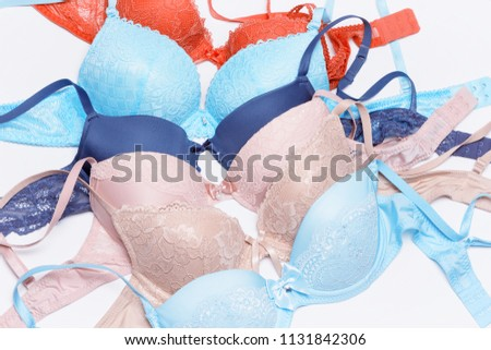 Set of lace push-up bras on white. Various pastel colored brassieres. Top view