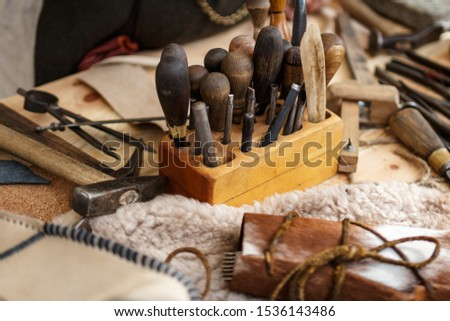 Set of leather working tools on working desk #1536143486