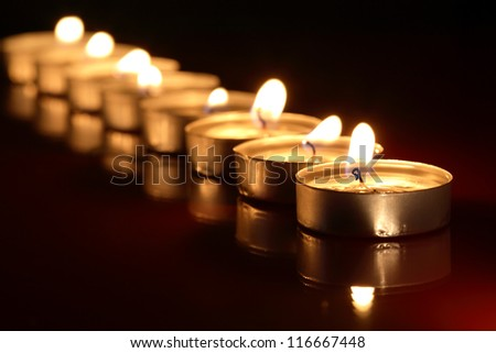 Set of lighting candles in a row on dark background with reflection