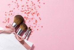 Set of make up brushes in white gift bag with pink ribbon and shining decorations on pink pastel background with copy space for your text. Beautiful holiday background.
