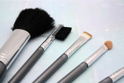 Set of makeup brushes on lightblue background. Space for text.