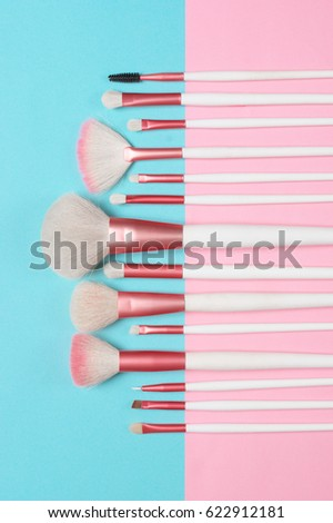 Shutterstock Set of makeup brushes on pink and aqua colored composed background. Top view point, flat lay.