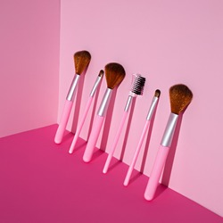Set of makeup brushes on pink colored composed background. Minimal make up, beauty or cosmetic studio concept. Top view, flat lay, isometric view.