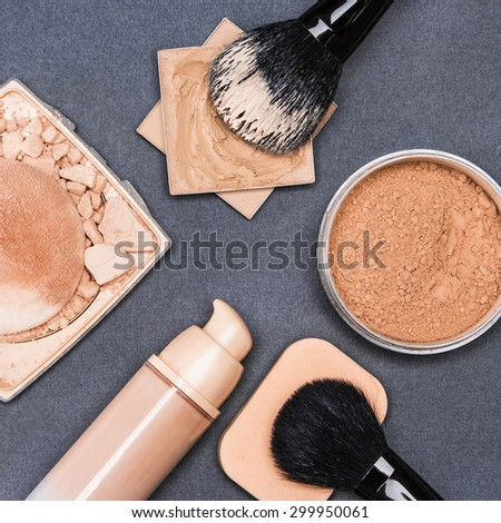 Set of makeup products to even out skin tone and complexion: concealer, corrector, open cream foundation bottle, jar of loose powder, crushed compact powder with makeup brushes and cosmetic sponge