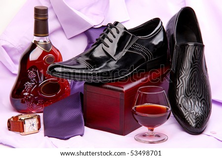 Set of male shoes, bottle and glass of brandy, and male wristwatch placed on a violet shirt with a tie