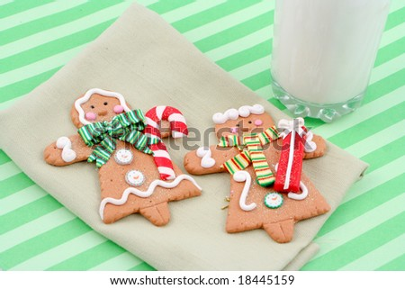 set of man and woman christmas gingerbread cookies on a napkin, with tall glass of cold milk