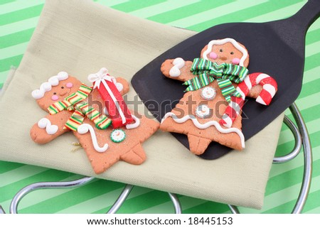 set of man and woman christmas gingerbread cookies, one is on a spatula fresh out of the oven