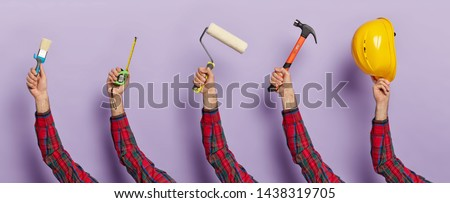 Set of mans hands hold building equipment against purple background. Tools for reconstruction and repairing. Unrecognizable builder with brush, measuring tape, paint roller, hammer and hardhat