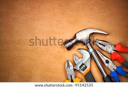 Set of manual tools over a wood panel with space for text