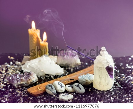 Set of many different psychic things on black background. Amethyst crystal pendulum, hand made rune stones, burning beeswax candles, crystal clusters, smoking incense. Spiritual healer concept.