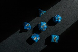Set of marbled blue role-playing game dice on a black surface lit by a beam of sunlight
