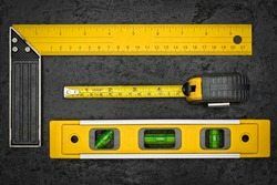 Set of measuring tools on a textured black metallic background