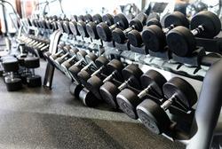 Set of metal dumbbells. Close up many dumbbell on rack in sport fitness center. Gym equipment concept