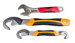 Set of metal hand tools for screwing and tightening nut or bolt isolated on a white background. Closeup of adjustable end wrench with red grip and two self-adjusting spanners with yellow black handle.