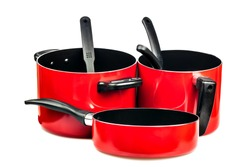 Set of metallic red cooking pots and pans isolated on white