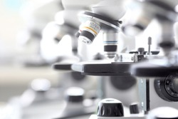 Set of microscopes standing in row in school chemist classroom closeup