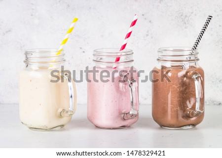 Set of milkshake in mason jars. Banana, chocolate and strawberry milkshakes. Summer dessert. Healthy food.