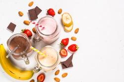 Set of milkshake or smoothie in mason jars. Banana, chocolate and strawberry milkshakes with nuts. Summer dessert. Healthy food. Top view.