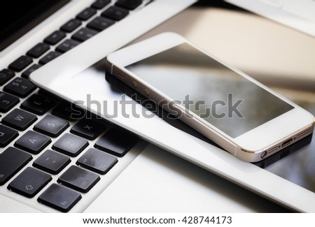 set of modern computer devices - laptop, tablet and mobile phone close up, retro toned - Shutterstock ID 428744173