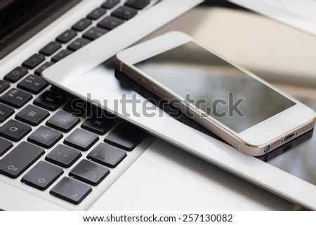 set of modern computer devices  - laptop, tablet and phone close up #257130082