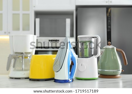 Set of modern home appliances on white marble table in kitchen stock photo