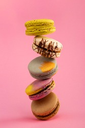 Set of multi-colored macarons on a pink background. Classic French dessert. French sweet delicacies.  Macaroons, flavored cookies floating in the air.