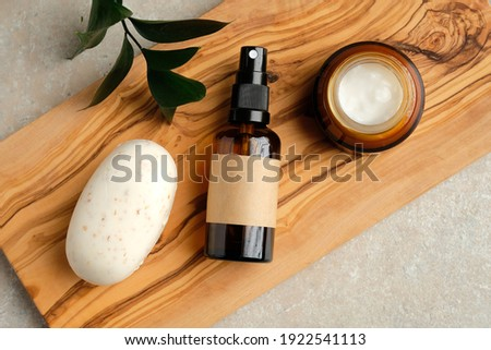 Set of natural organic SPA beauty products on wooden board. Homemade soap, moisturizer cream jar, amber glass spray bottle, green leaf on wooden board. Сток-фото ©