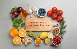 Set of natural products and wooden board with text Boost Your Immune System on grey table, flat lay