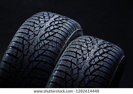 Set of new winter tires on black background with contrasty lighting. Close up product photograph of unused tyres #1282614448