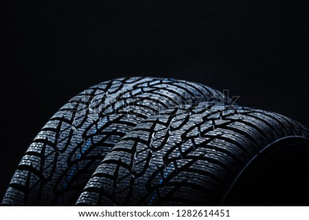 Set of new winter tires on black background with contrasty lighting. Close up product photograph of unused tyres #1282614451