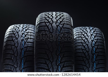 Set of new winter tires on black background with contrasty lighting. Close up product photograph of unused tyres #1282614454
