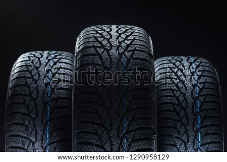 Set of new winter tires on black background with contrasty lighting. Close up product photograph of unused tyres #1290958129