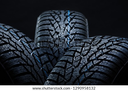 Set of new winter tires on black background with contrasty lighting. Close up product photograph of unused tyres #1290958132