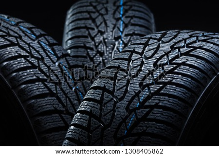 Set of new winter tires on black background with contrasty lighting. Close up product photograph of unused tyres #1308405862