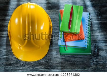 Set of notepads pen hard hat on wooden board.