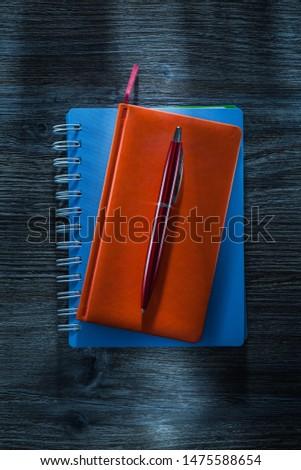Set of notepads pen on vintage wooden board.