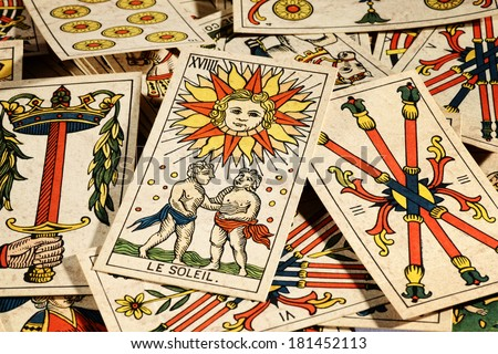 Set of old tarot cards lying in a scattered heap with their designs uppermost and a picture of the sun on top Stockfoto ©
