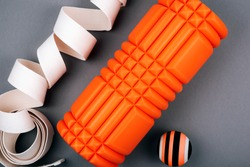 Set of orange myofascial release and massage ball,  bumpy foam massage roller for trigger points and white belt  over grey background.  Self body care massage and stress, pain relief.  Sport concept.