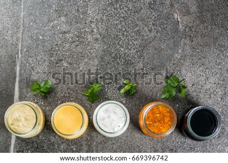 Set of organic healthy dietary dressings for salad: sauce vinaigrette, mustard, mayonnaise with spices or ranch, balsamic or soy, basil with yogurt. On a dark stone table. Top view copy space #669396742