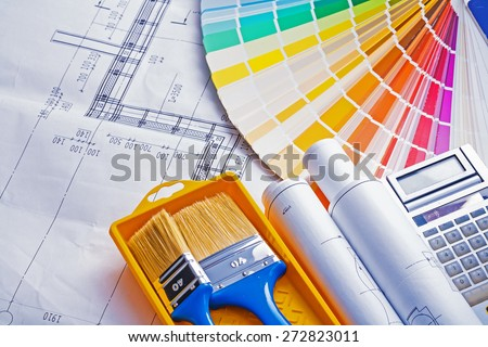 set of painting tools paint brushes in tray rolls blueprints color palette calculator