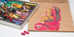 Set of pastels with bright crayons and a drawing of a girl with pink hair and a jacket on crane beige paper, on a white background