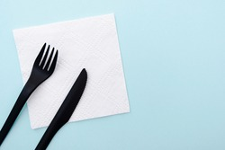 Set of plastic cutlery black fork and knife on white paper napkin and  blue background, top view, space for text.