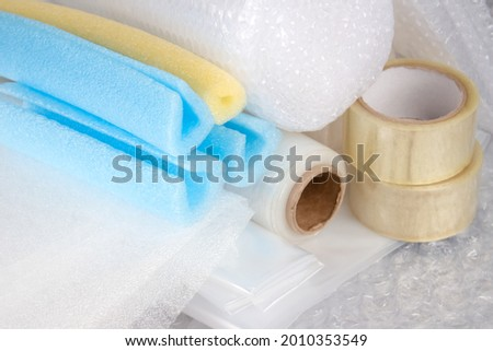 Set of plastic packaging materials - plastic stretch film rolls, foamed polyethylen sheets and rolls, transparent scotch tape, foam edge protectors, small and large bubblewrap rolls. Selective focus